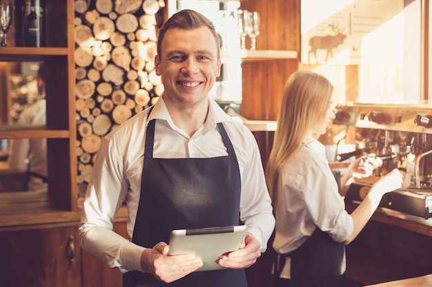 Profesjonalny barista. młoda kobieta i mężczyzna w fartuchach pracujących na ladzie barowej. mężczyzna trzymający komputer typu tablet