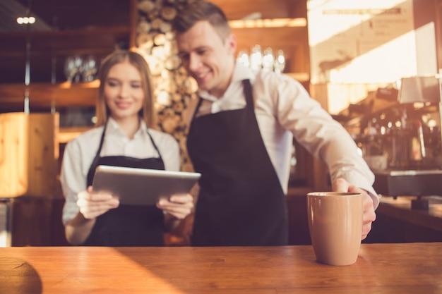 Profesjonalny barista. młoda kobieta i mężczyzna w fartuchach, uśmiechając się i stojąc przy barze. kobieta korzystająca z komputera typu tablet