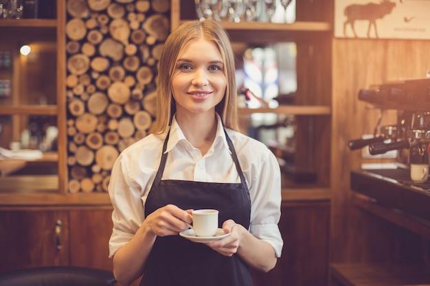 Profesjonalny barista. młoda kobieta w fartuchu trzymająca filiżankę kawy i patrząca na kamerę