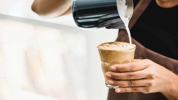 Profesjonalny barista parzenia kawy latte art