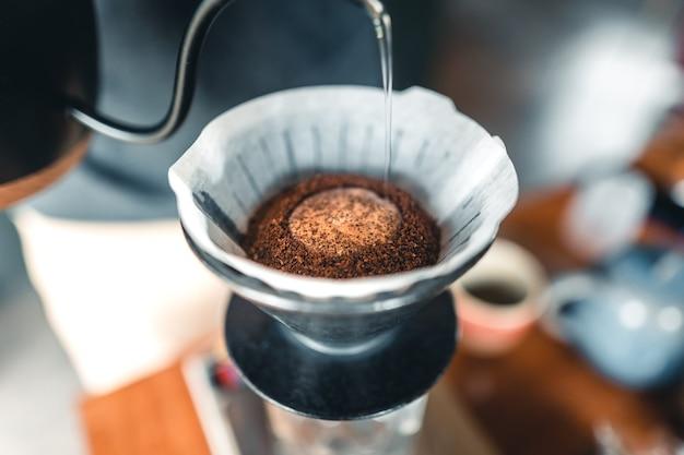 Profesjonalny barista przygotowujący kawę przelewową przez ekspres do kawy i czajnik ociekowy