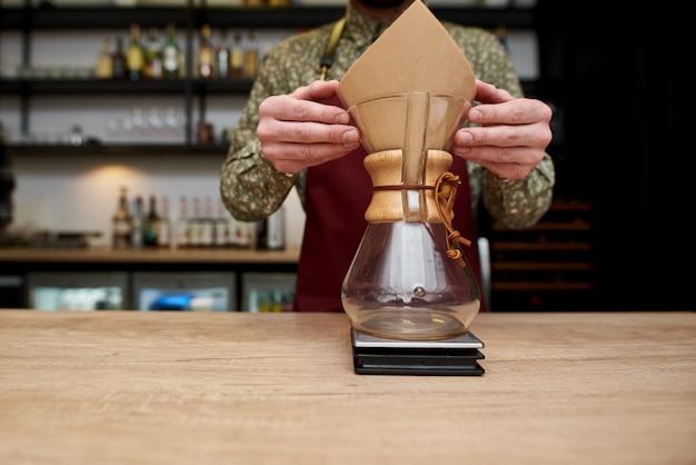 Profesjonalny barista przygotowujący kawę za pomocą chemex zalej ekspres do kawy i czajnik. alternatywne sposoby parzenia kawy. koncepcja kawiarni.