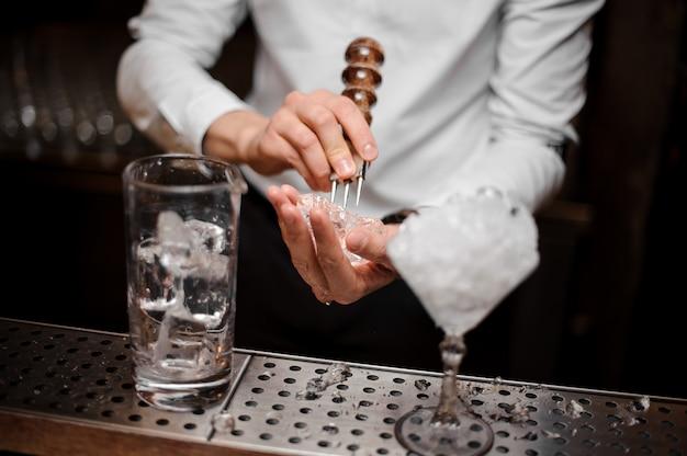 Profesjonalny barman łamający kostkę lodu za pomocą specjalnego narzędzia