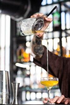 Profesjonalny barman miesza zimny koktajl łyżką kilka butelek napojów alkoholowych