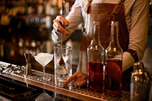 Profesjonalny barman mieszający napój alkoholowy z lodem w szklanym naczyniu pomiarowym w pobliżu butelek