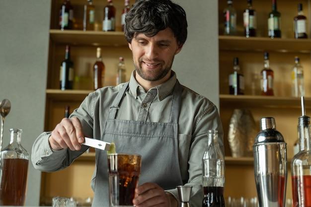 Profesjonalny barman ozdabia koktajl limonką barman przygotowuje koktajl z whisky i colą przygotowując koktajle w barze