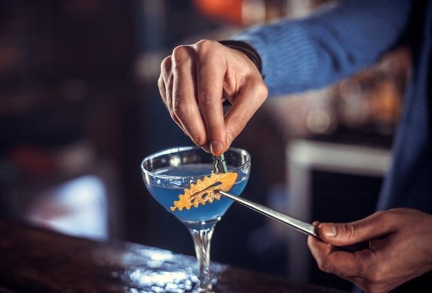Profesjonalny barman ozdabia kolorową miksturę w nocnym klubie