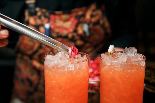 Profesjonalny barman przygotowuje dwa czerwone koktajle i ozdabia je żywym kwiatem. koktajle są w barze.