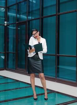 Profesjonalny biznes afro kobieta w eleganckiej białej kurtce i spódnicy z teczką z dokumentami w dłoniach