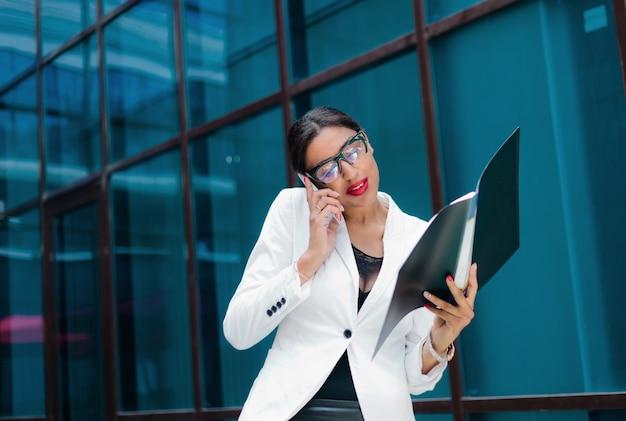 Profesjonalny biznes kobieta w eleganckiej białej kurtce i spódnicy z folderem z dokumentami w dłoniach