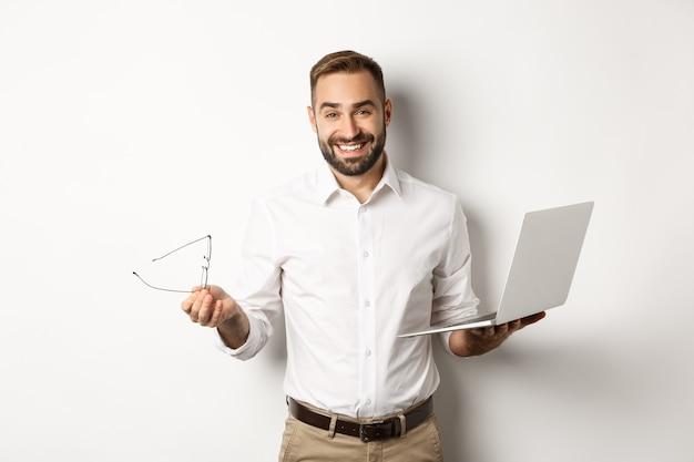 Profesjonalny biznesmen pewność wykonywania pracy na laptopie, patrząc zadowolony, stojąc