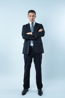 Profesjonalny biznesmen. pomyślny miły inteligentny biznesmen, stojąc z rękami skrzyżowanymi i patrząc na ciebie, pokazując swoją pewność siebie