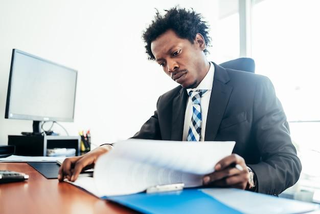 Profesjonalny biznesmen pracy z niektórymi plikami i dokumentami w jego nowoczesnym biurze. pomysł na biznes.