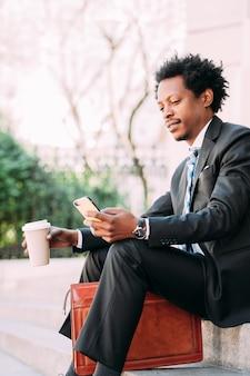 Profesjonalny biznesmen przy użyciu swojego telefonu komórkowego i picia filiżanki kawy siedząc na zewnątrz