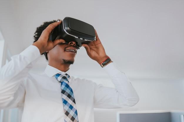 Profesjonalny biznesmen za pomocą zestawu słuchawkowego wirtualnej rzeczywistości w nowoczesnym biurze. koncepcja biznesowa i technologiczna.