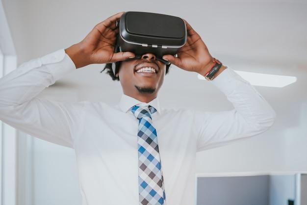 Profesjonalny biznesmen za pomocą zestawu słuchawkowego wirtualnej rzeczywistości w nowoczesnym biurze