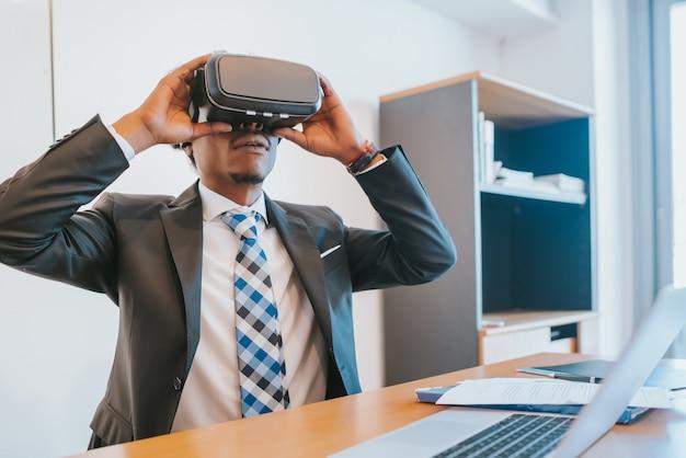 Profesjonalny biznesmen za pomocą zestawu słuchawkowego wirtualnej rzeczywistości w nowoczesnym biurze.