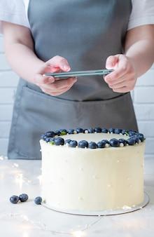 Profesjonalny bloger kulinarny robiący zdjęcia na smartfonie. białe ciasto z twarogiem i świeżymi jagodami.
