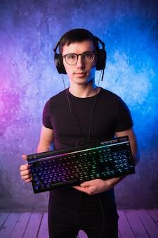 Profesjonalny boy gamer trzyma klawiaturę do gier nad kolorową różową i niebieską neonową ścianą.
