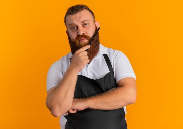Profesjonalny brodaty fryzjer w fartuchu, czeszący brodę z pewnym siebie wyrazem, stojący nad pomarańczową ścianą