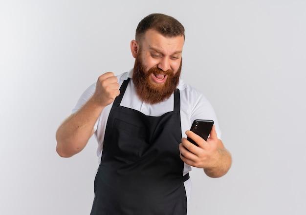 Profesjonalny brodaty fryzjer w fartuchu patrząc na ekran swojego smartfona szczęśliwy i podekscytowany zaciśniętą pięścią, ciesząc się jego sukcesem stojącym nad białą ścianą