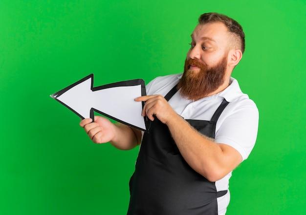 Profesjonalny brodaty fryzjer w fartuchu trzyma dużą strzałkę skierowaną w lewo stojącego nad zieloną ścianą