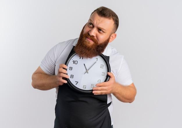 Profesjonalny brodaty fryzjer w fartuchu trzyma zegar ścienny patrząc na bok bardzo zaniepokojony stojąc na białej ścianie