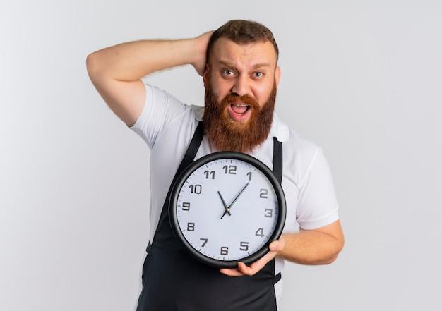 Profesjonalny brodaty fryzjer w fartuchu trzyma zegar ścienny wyglądający na zdezorientowanego i bardzo niespokojnego stojącego nad białą ścianą