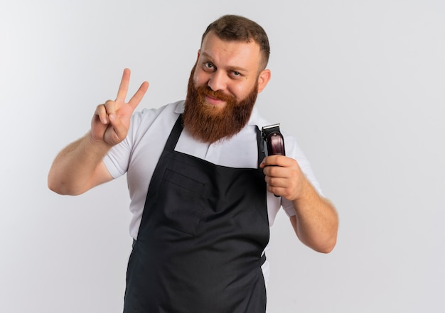 Profesjonalny brodaty fryzjer w fartuchu trzymając maszynę do cięcia włosów pokazując znak zwycięstwa lub numer dwa uśmiechając się stojąc na białej ścianie