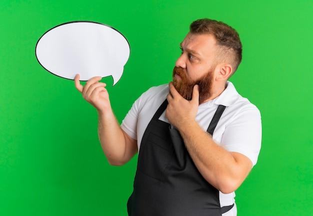 Profesjonalny brodaty fryzjer w fartuchu, trzymając pusty znak bańki, patrząc na niego zdziwiony stojąc nad zieloną ścianą