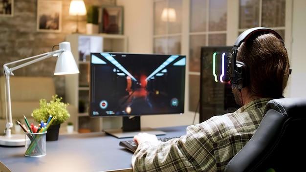 Profesjonalny brodaty gracz rozciągający się przed rozpoczęciem gry. mężczyzna siedzi na fotelu do gier.