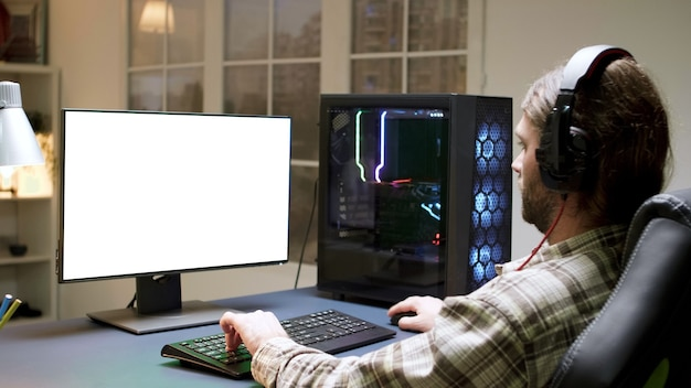Profesjonalny brodaty gracz z długimi włosami, grający w gry wideo na komputerze z zieloną makietą.