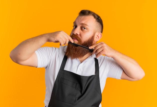 Profesjonalny brodaty mężczyzna fryzjer w fartuch czesanie brodę stojący nad pomarańczową ścianą
