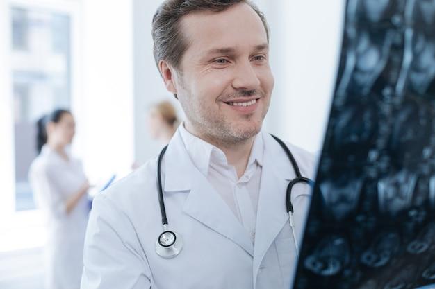 Profesjonalny brodaty uśmiechnięty neurochirurg pracuje w klinice i trzyma zdjęcie rentgenowskie, podczas gdy jego koledzy cieszą się rozmową za plecami
