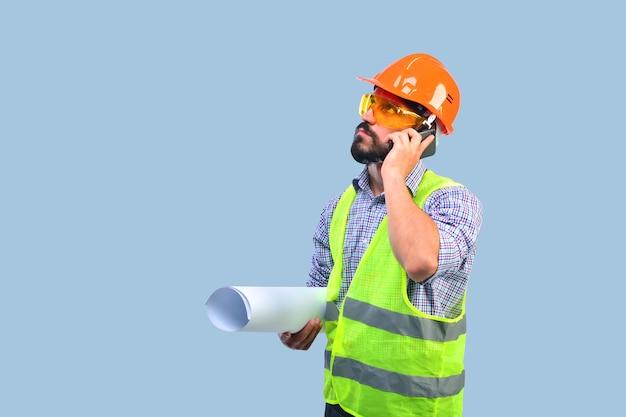 Profesjonalny budowniczy brygadzista trzymający projekt i rozmawiający telefon