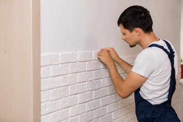 Profesjonalny budowniczy przyklejający dekoracyjną płytkę na ścianie. pracownik montuje dekoracyjną cegłę na ścianie
