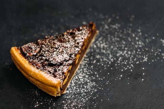 Profesjonalny catering. zbliżenie tarta orzechowa z melasą posypana cukrem pudrem.