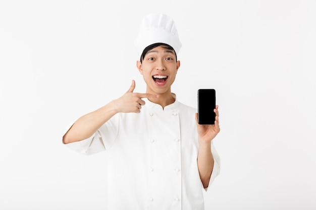 Profesjonalny chiński wódz w białym mundurze kucharza i kapelusz szefa kuchni trzymając telefon komórkowy na białym tle nad białą ścianą