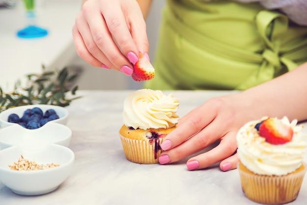Profesjonalny cukiernik dekorujący górę babeczki z truskawkami. domowe ciasto. kobieta gotowania ciast.
