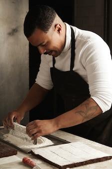 Profesjonalny czarny kondycjoner wkłada kawałek smacznego ciasta czekoladowego do cukru pudru w swojej rzemieślniczej cukierni