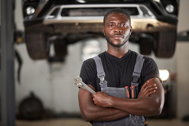 Profesjonalny czarny mechanik samochodowy patrząc na kamery