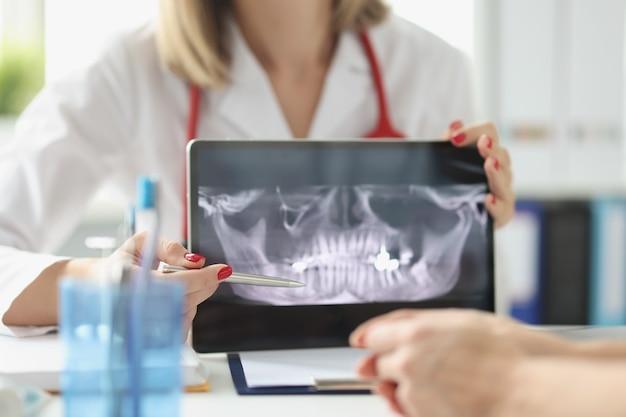 Profesjonalny dentysta pokazuje pacjentom zdjęcia rentgenowskie szczęk i zębów za pomocą cyfrowego tabletu medycznego