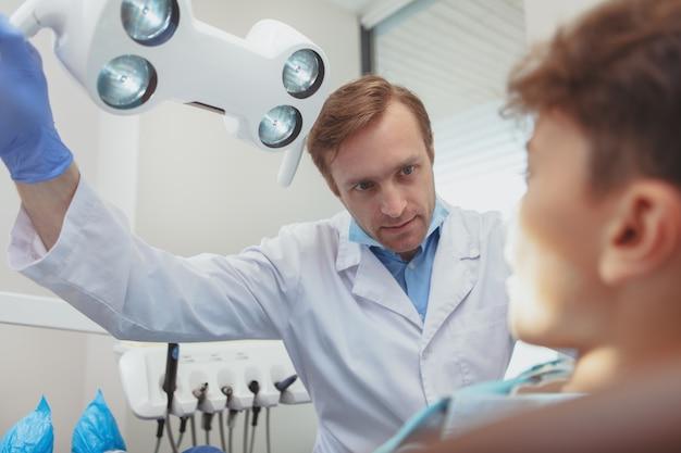 Profesjonalny dojrzały dentysta dostosowuje lampę dentystyczną przed badaniem jego małego pacjenta