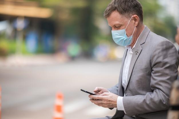 Profesjonalny dorosły biznesmen noszący chirurgiczną maskę na twarz w celu ochrony przed koronawirusem covid-19, pracownik biznesowy nowy normalny styl życia na tle miejskiego wieżowca, osoba w garniturze