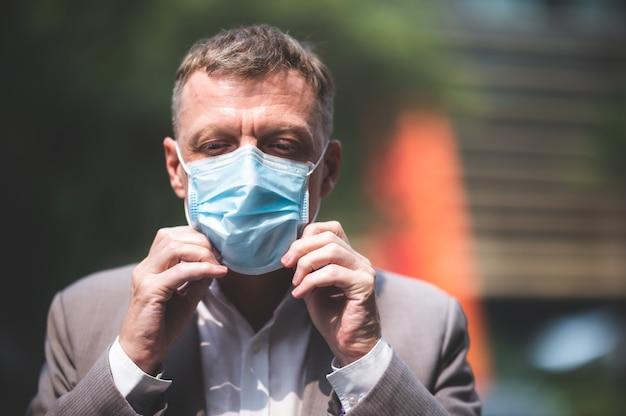 Profesjonalny dorosły biznesmen noszący chirurgiczną maskę na twarz w celu ochrony przed koronawirusem covid-19