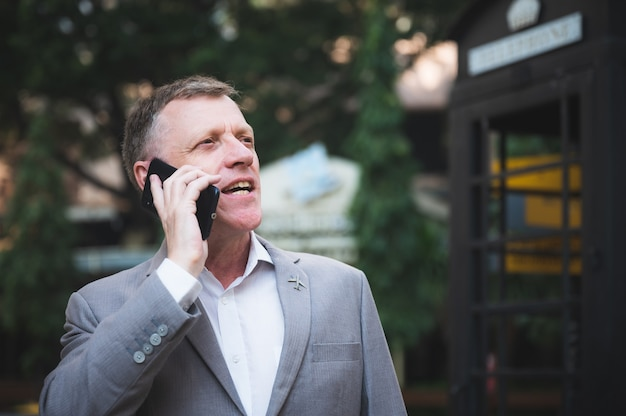 Profesjonalny dorosły biznesmen rozmawia ze smartfonem