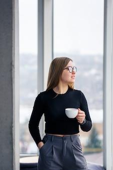 Profesjonalny dorosły kobieta picia kawy w koszuli i spodniach, stojąc przed dużymi szklanymi oknami.