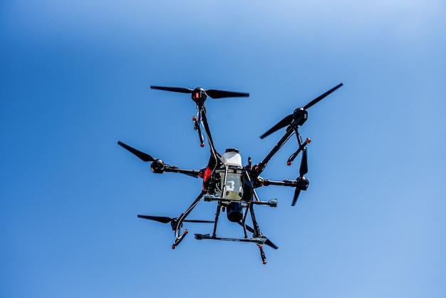 Profesjonalny dron rolniczy latający po błękitnym niebie