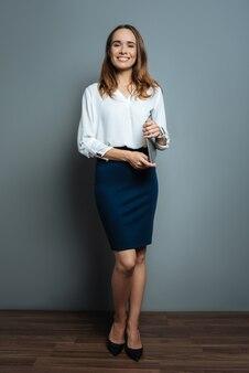 Profesjonalny dyrektor generalny. wesoła pozytywna inteligentna bizneswoman trzyma laptopa i patrzy na ciebie podczas pracy jako profesjonalny dyrektor generalny