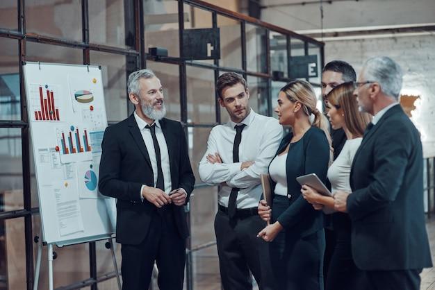 Profesjonalny ekspert biznesowy przedstawiający raport analityczny podczas wspólnej pracy z kolegami w holu biurowym